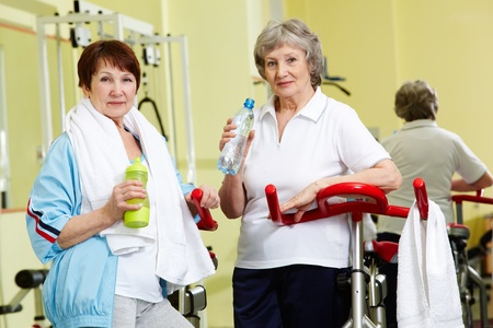 Portrait of senior females with plastic bottles looking at camera in gym photo
