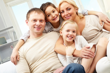 A family of four embracing and smiling at home photo