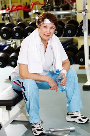 Portrait of aged woman with bottle of water in sport club photo