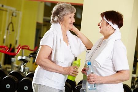 amigas conversando: Retrato de mujeres senior refrescantes despu�s de entrenamiento en el gimnasio