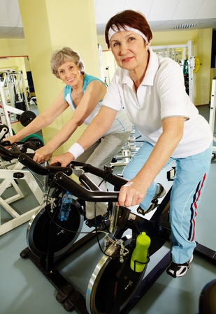 Portrait of senior females doing physical exercise on special equipment in club photo