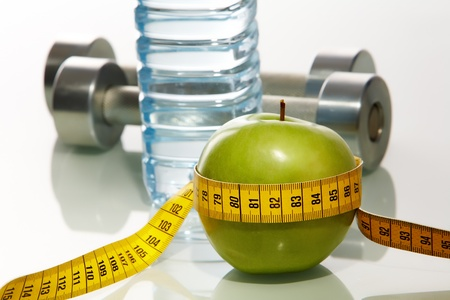 Close�up of green apple with measuring tape and two metal barbells on background  photo