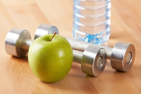 Close–up of green apple with plastic bottle and two metal barbells on background  photo