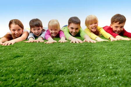 Group of happy children lying on a grass and stretching their arms  photo