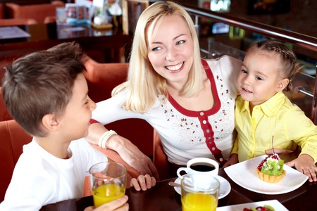Portrait of happy woman with her two cute children in cafe Stock Photo - 9726247