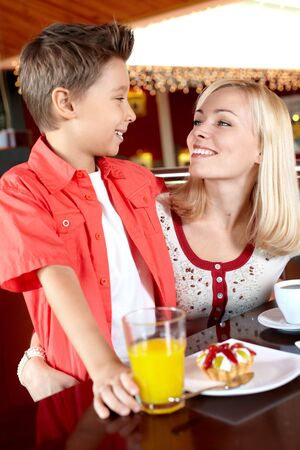 Portrait of cute lad and his mother in cafe photo