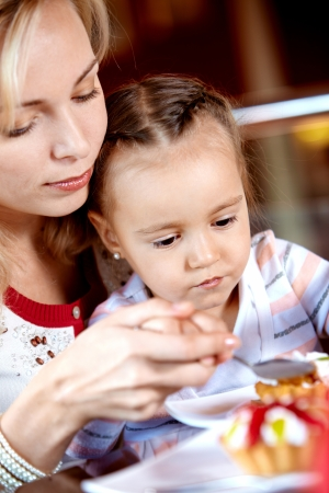 Portrait of cute girl eating cupcake with her mother near by in cafe photo