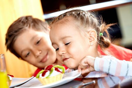 Portrait of cute girl looking at tasty cake with her brother near by Stock Photo - 9726240
