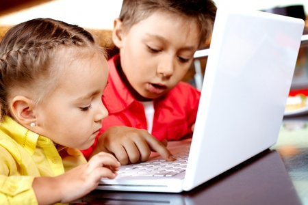 Portrait of cute children typing on laptop Stock Photo - 9726246