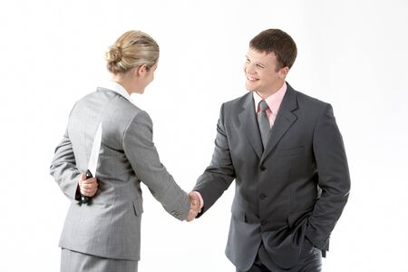 Portrait of business partners handshaking while female holding knife behind her back photo