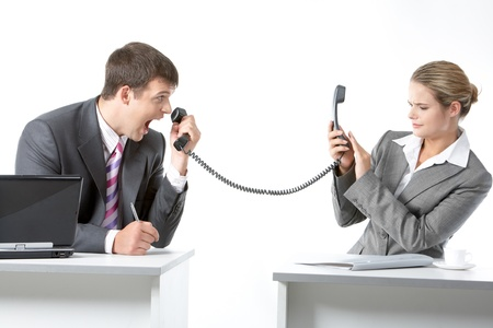 people interacting: Portrait of angry boss shouting into telephone receiver at his secretary Stock Photo