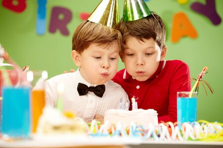 Portrait of happy boys on birthday party blowing at candles on cake photo