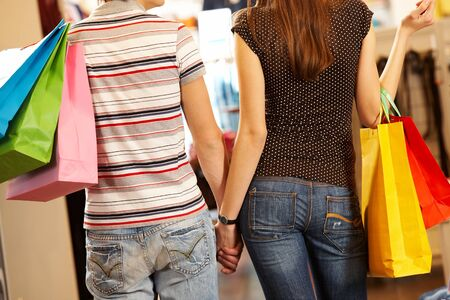 Backs of husband and wife shopping in the mall photo