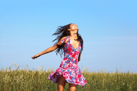 glad: Photo of glad girl in colorful dress enjoying life in wheat meadow in summer