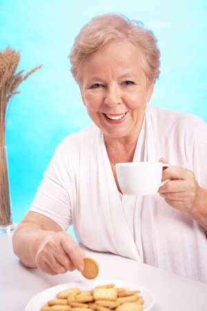 Portrait of friendly woman drinking tea with cookies and looking at camera photo