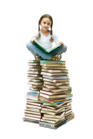 literatura: Portrait of cute girl sitting on pile of books and looking at camera Reklamní fotografie