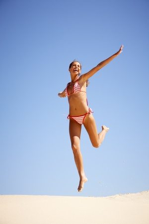 swimsuit: Portrait of joyful girl leaping on sandy beach during summer vacation and laughing