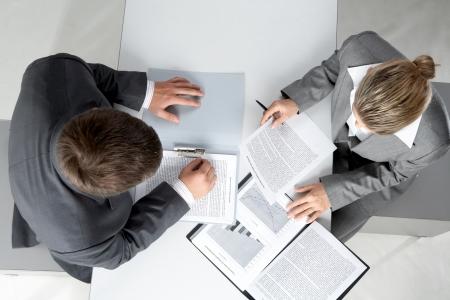 Sopra l'angolo di due partner d'affari di pianificazione lavoro a soddisfare