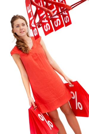 Young shopper carrying bags and looking at hangers with discount symbols photo