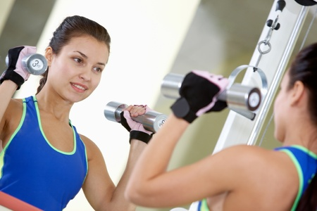 Portrait of young female with dumbbells doing exercises in gym in front of mirror Stock Photo - 9726345