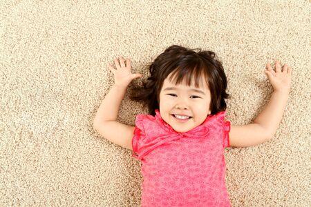 Portrait de Mignon enfant riant tandis que mentir sur tapis Banque d'images