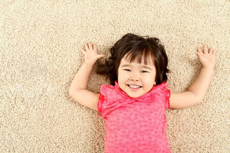 Portrait of cute child laughing while lying on rug Stock Photo - 9726462