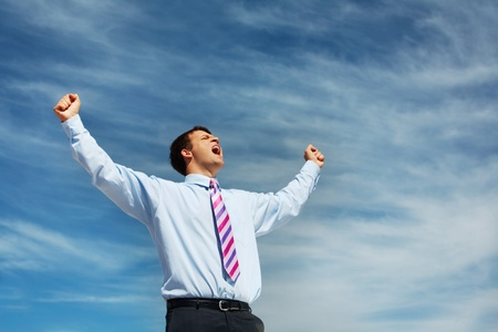 glad: Photo of happy winner screaming from joy on background of blue summer sky Stock Photo