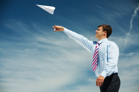 launch: Image of businessman letting paper airplane fly and looking at it on background of blue sky