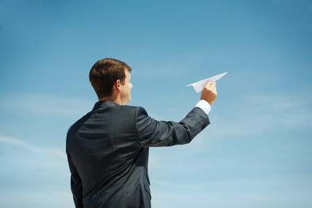 throwing: Photo of businessman holding paper aircraft in stretched hand before launching it Stock Photo