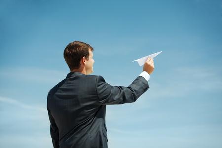 papierflugzeug: Photo of Gesch�ftsmann im Besitz Papier Flugzeug in gestreckter Hand vor dem Start Lizenzfreie Bilder