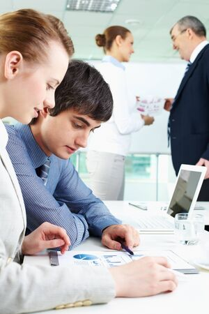 Portrait of confident man looking at document with female near by in working environment photo