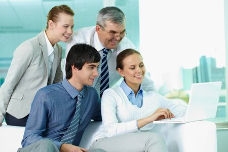 Portrait of several colleagues looking at laptop screen in office photo