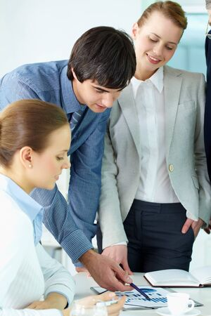 Portrait of confident man pointing at document surrounded by females in office Stock Photo - 9727000