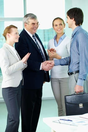 agreeing: Photo of successful businessmen handshaking after striking deal with applauding women near by