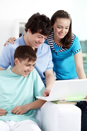 Three teenagers studying with computer photo