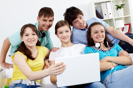 Portrait of five teens sitting on sofa with a laptop photo