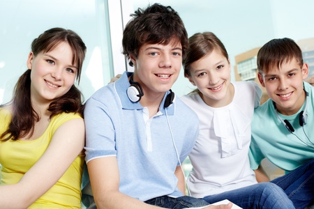 Portrait of four smiling teenagers looking at camera photo