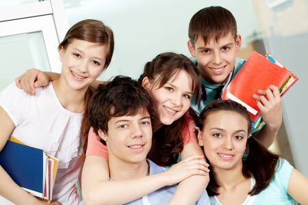 highschool: Portrait of five students embracing looking at camera and smiling