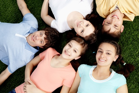 High angle view of five happy teens lying on grass  photo