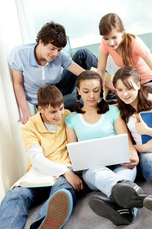 Five friends sitting in room and looking at laptop photo