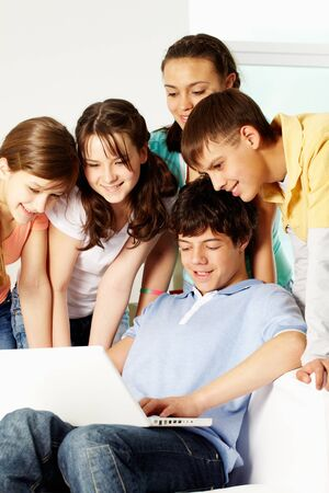 A boy showing something on a laptop to his friends photo