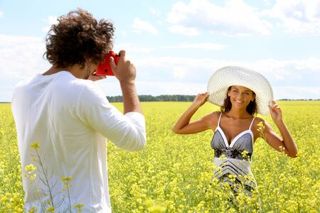 Image of young guy taking photos of pretty girl on yellow field at summer photo