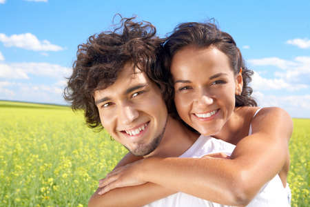 Portrait of young man giving beautiful woman piggyback in the field  photo