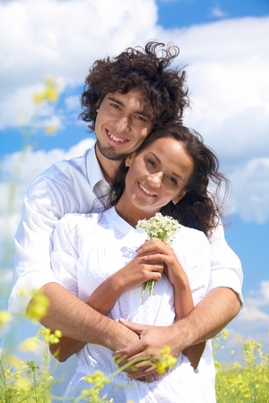 Young man hugging charming lady in white clothing while both looking at camera with happy smiles Stock Photo - 9726590