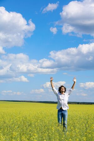 View of smiling man raising his hands while standing in the field