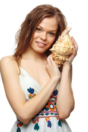 Portrait of a young girl holding a shell, looking at camera and smiling photo