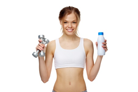 Portrait of a slim girl holding a bottle of milk and dumbbells, looking at camera and smiling Stock Photo - 9726542
