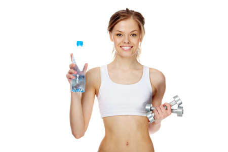 Portrait of woman with smile holding bottle of water and dumbbells  photo