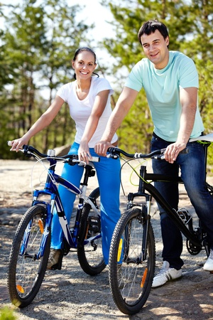 A young couple on bicycles looking at camera and smiling photo