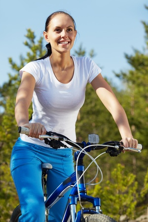 Pretty young woman riding a bicycle photo